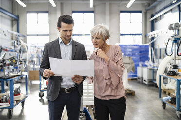 Businessman and senior woman looking at plan in a factory - DIGF05723