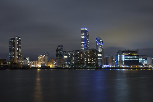 United Kingdom, England, London,  Docklands, Isle of Dogs, modern apartment tower and office building at River Thames at night - WIF03821