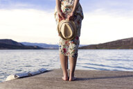 Back view of barefoot young woman standing on jetty holding summer hat, partial view - JSRF00115
