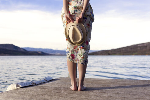 lake of Cellers, LLeida,Catalonia, Spain,Close-up of young woman holding straw hat on wooden pier near to lake. - JSRF00115