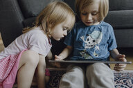 Brother and little sister sitting on the floor at home using digital tablet - JLOF00305