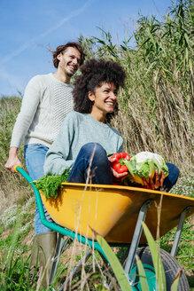 Woman sitting in wheelbarrow, holding fresh vegetables, man pushing her - GEMF02708