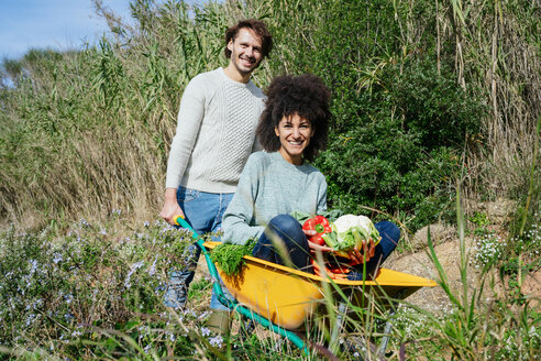 Woman sitting in wheelbarrow, holding fresh vegetables, man pushing her - GEMF02711