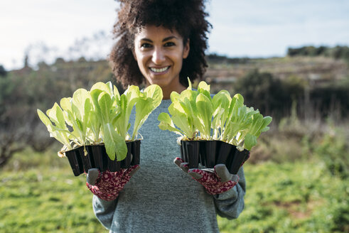 Smiling woman holding lettuce seedlings in a vegetable garden - GEMF02726