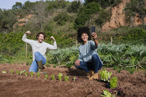 Couple taking selfies of planting lettuce seedlings in an vegetable garden - GEMF02768