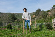 Young farmer standing in vegetable garden with straw hat and a hoe - GEMF02771