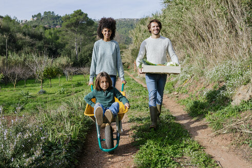 Family walking on a dirt track, pushing wheelbarrow, carrying crate with vegetables - GEMF02783