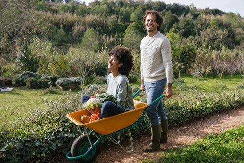 Woman sitting in wheelbarrow, holding fresh vegetables, man pushing her - GEMF02786