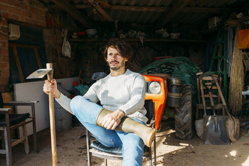 Man with a hoe sitting in a shed with a tractor - GEMF02789