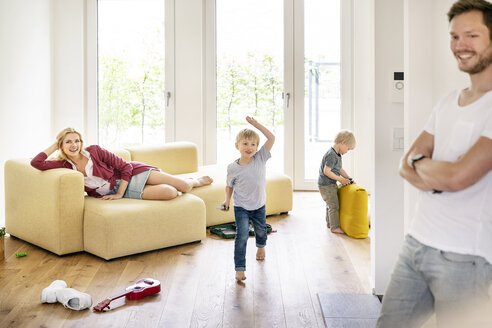 Happy family moving into their new home, parents playing with their kids - PESF01439