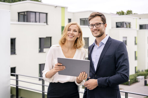 Real estate agent standing on a balcony with customer, looking at digital tablet - PESF01466