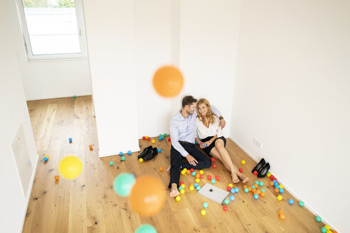 Business couple sitting on floor of their new home with colorful balls - PESF01475