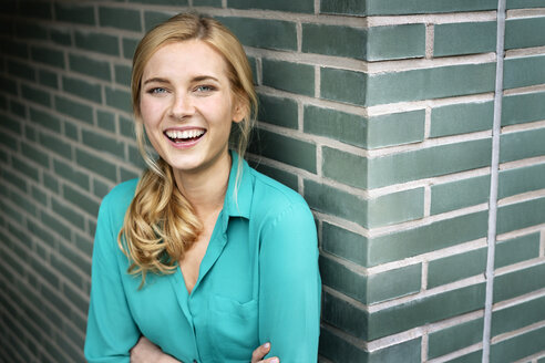 Portrait of a cheerful young woman, leaning against wall with arms crossed - PESF01484