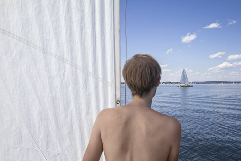 Germany, Bavaria, Chiemsee, man looking to another sailing boat - MAMF00395