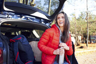 Happy woman sitting in car trunk during road trip with thermos flask - BSZF00900