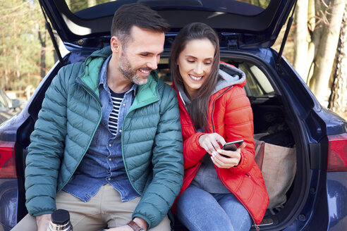 Couple using smartphone while sitting in car trunk during road trip - BSZF00903