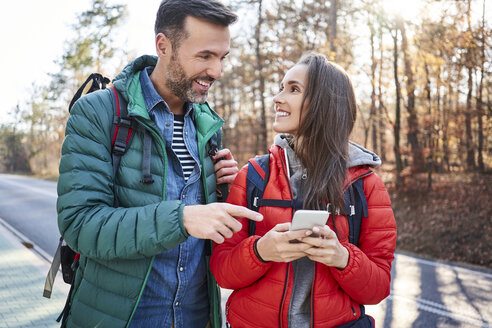 Happy couple checking smartphone on a road in the woods during backpacking trip - BSZF00912