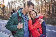 Happy couple embracing on a road in the woods during backpacking trip - BSZF00915