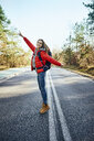Happy woman standing in middle of an empty road during backpacking trip - BSZF00918