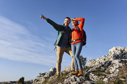 Happy couple on a hiking trip in the mountains standing on rock enjoying the view - BSZF00933