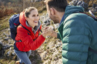 Man helping girlfriend climbing rock on a hiking trip in the mountains - BSZF00936