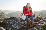Happy woman on a hiking trip in the mountains sitting on rock having a break - BSZF00942