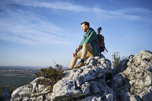 Man on a hiking trip in the mountains sitting on a rock enjoying the view - BSZF00945