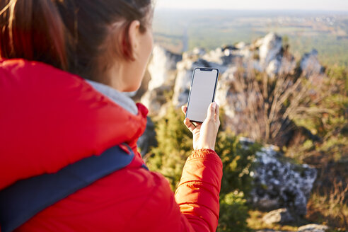 Close-up of woman using phone while on hiking trip - BSZF00948