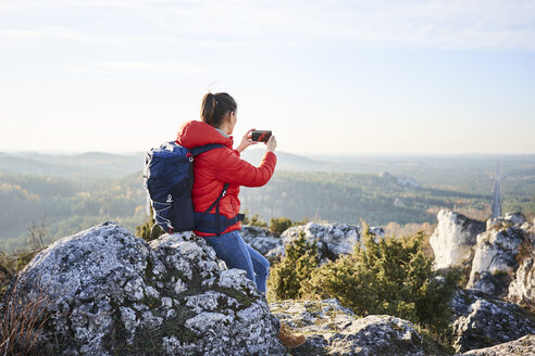 Woman on a hiking trip in the mountains taking smartphone photo - BSZF00951