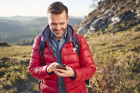 Smiling man on a hiking trip in the mountains checking cell phone - BSZF00957