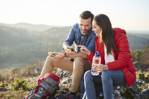 Happy couple on a hiking trip in the mountains taking a break looking at cell phone - BSZF00960
