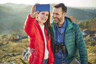 Happy couple on a hiking trip in the mountains taking a selfie - BSZF00963