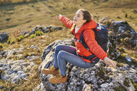 Woman on a hiking trip in the mountains resting on a rock - BSZF00966