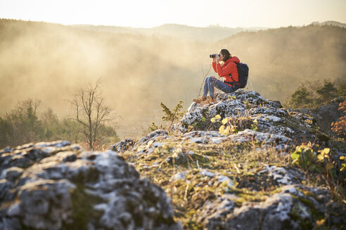 Woman on a hiking trip in the mountains sitting on rock looking through binoculars - BSZF00969