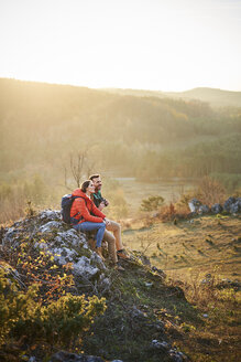 Couple on a hiking trip in the mountains having a break sitting on rock - BSZF00978