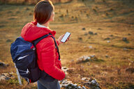 Woman with cell phone on a hiking trip in the mountains - BSZF00984