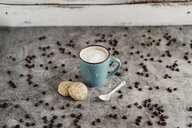 Cup of white coffee, whole meal cookies, porcelain spoon and scattered coffee beans - AFVF02359