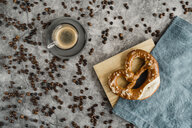 Cup of black coffee, coffee beans and pretzel on napkin and wooden board - AFVF02365