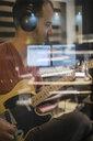 Focused male guitarist with headphones playing in recording studio - HEROF21007