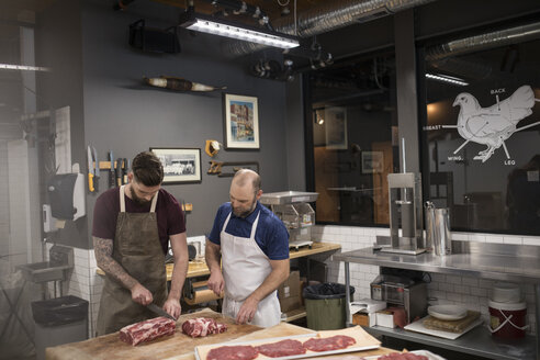 Male butchers cutting raw red meat in butcher - HEROF21016
