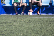 Legs of two football players sitting on bench at football field - ABZF02176