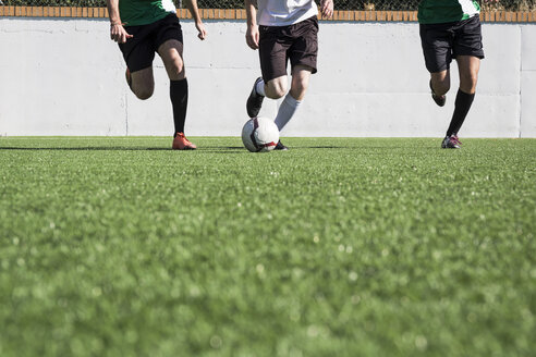 Crop sportive players in motion of running on green grass kicking ball around. - ABZF02185