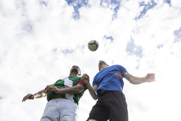 Football players jumping to head the ball during a football match - ABZF02194