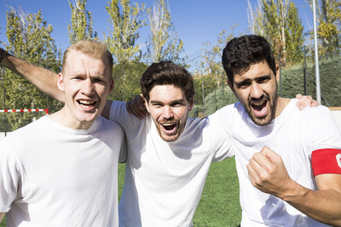 Portrait of football players cheering on football field - ABZF02209