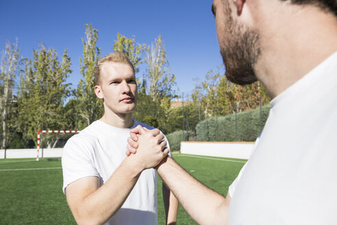 Two football players shaking hands on football field - ABZF02221