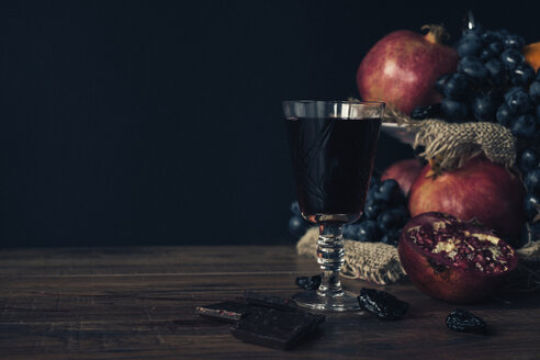 Fruits and glass of vine on dark wood - MOMF00624