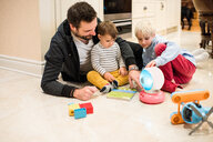 Father and sons playing with toys on floor - ISF20683