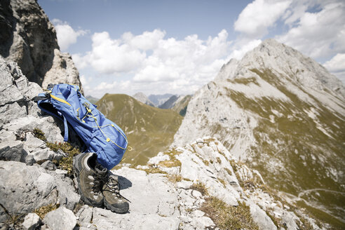 Austria, Tyrol, backpack and hiking boots in mountainscape - FKF03257
