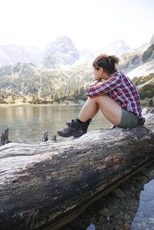 Austria, Tyrol, woman sitting on tree trunk at lake Seebensee - FKF03266