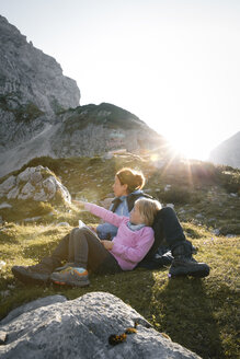 Austria, Tyrol, mother with daughter resting in mountainscape at sunset - FKF03284